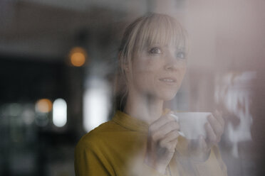 Portrait of a beautiful blond woman standing at window, drinking coffee - JOSF03162