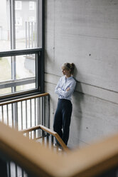 Successful businesswoman leaning on wall, looking out of window, with arms crossed - JOSF03177
