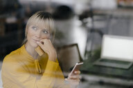Blond businesswoman sitting at window, doing a paymant with smartphone and creditcard - JOSF03180