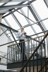 Businesswoman standing in loft office, using smartphone - JOSF03183