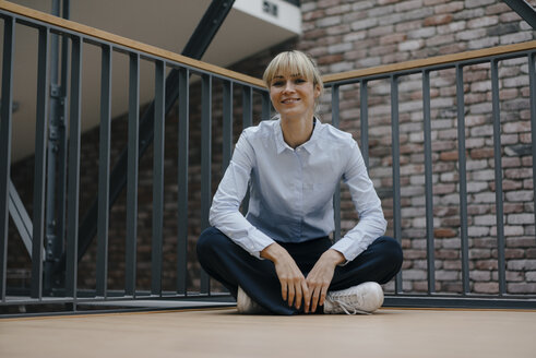 Relaxed businesswoman sitting cross-legged on the floor - JOSF03189