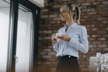 Businesswoman standing in office, taking a break, drinking coffee - JOSF03204