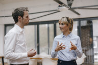 Businessman and woman standing in office, discussing - JOSF03219