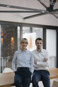 Successful businessman and woman standing in office, with arms crossed - JOSF03243
