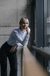 Confident businesswoman standing at window, thinking - JOSF03249