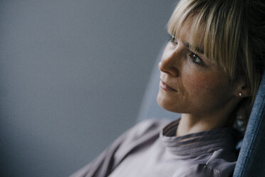 Blond woman sitting in armschair, looking sad, close up - JOSF03264
