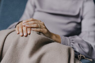 Folded hands of a woman on a blanket over her knees - JOSF03267