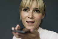 Portrait of a blond businesswoman, using smartphone - JOSF03273