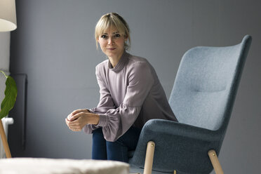 Blond woman sitting in armchair, looking at camera - JOSF03276