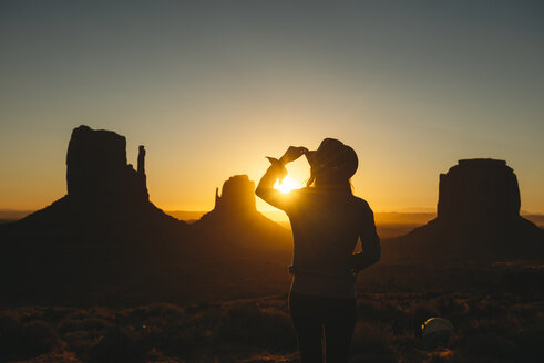 USA, Utah, Monument Valley, silhouette of woman with cowboy hat  watching sunrise - GEMF02891