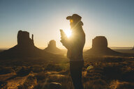 USA, Utah, Monument Valley, silhouette of woman with cowboy hat using mobile phone at sunrise - GEMF02900