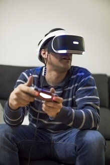Young man wearing VR glasses sitting on couch at home playing video game - ACPF00488