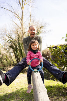 Portrait of father and little daughter having fun together on seesaw - GEMF02901