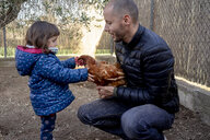 Father and little daughter with chicken at hen farm - GEMF02904