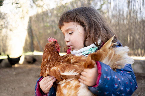 Toddler girl talking to chicken on her arms - GEMF02907