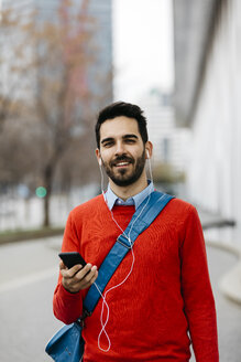 Casual businessman commuiting in the city, using earphones and smartphone - JRFF02839