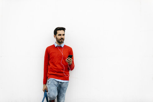 Casual businessman leaning on wall, using earphones and smartphone - JRFF02842