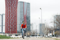 Casual businessman commuting in the city, using his folding bike - JRFF02845
