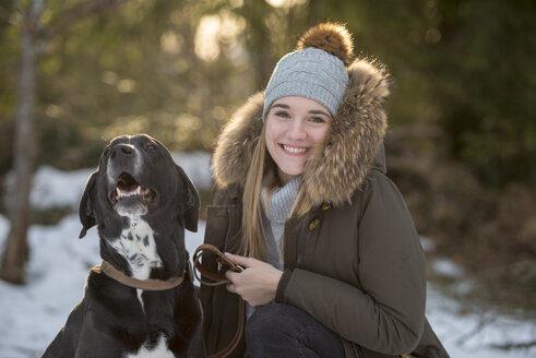 Portrait of happy young woman wwith dog at winter forest - LBF02433