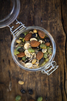 Preserving jar of roasted soy beans, seeds and nuts on wood - LVF07876