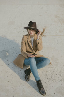 Young hipster woman sitting on the ground holding a phone - AHSF00047