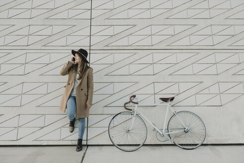 Young hipster woman speaking by phone near to a bicycle - AHSF00053