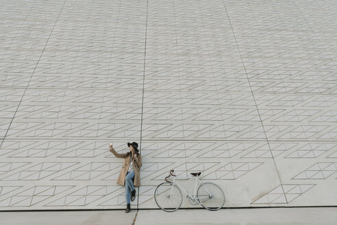 Young hipster woman near to a bicycle making a selfie - AHSF00056