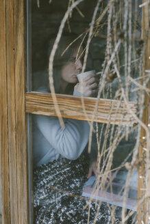 Woman behind window drinking tea - ALBF00821