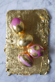 Four painted Easter eggs on golden background and marble - JTF01194