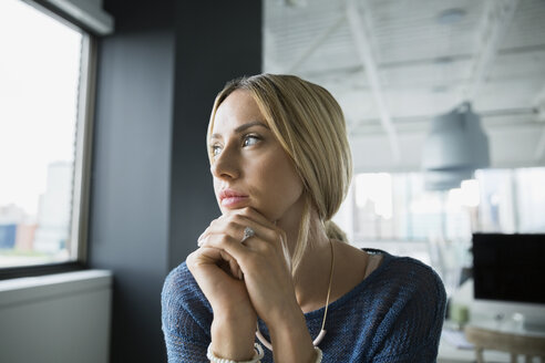 Pensive businesswoman looking out office window - HEROF28715