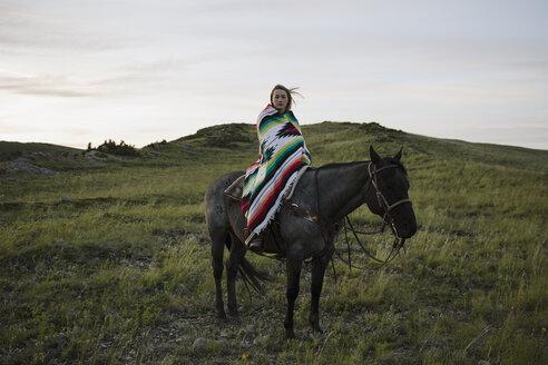 Portrait female rancher on horseback wrapped in blanket - HEROF28724