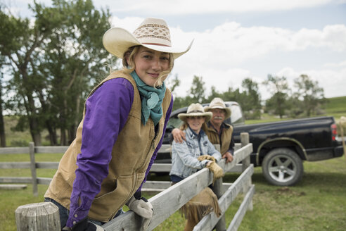 Portrait confident rancher family at rural fence - HEROF28727