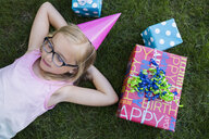 Overhead view girl party laying birthday gifts grass - HEROF28730