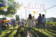 Neighbors entering under Welcome sign party in park - HEROF28745