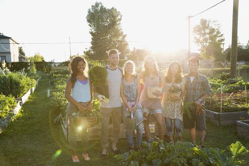 Portrait smiling friends harvesting vegetables in community garden - HEROF28748