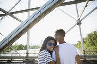 Portrait smiling couple on sunny bridge - HEROF28802