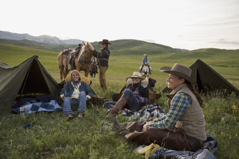 Female ranchers relaxing at campsite in remote field - HEROF28808