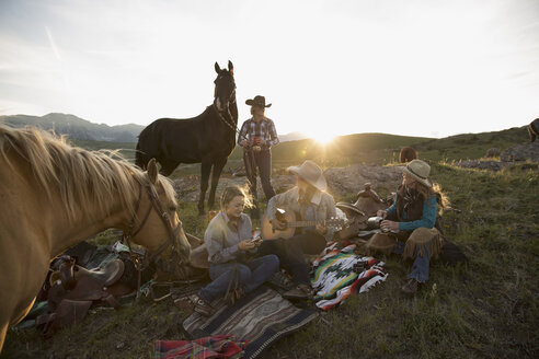 Female ranchers camping in remote field playing guitar - HEROF28829