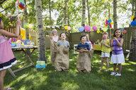 Kids enjoying sack race at backyard birthday party - HEROF28835