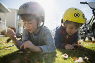 Brothers laying in grass playing with autumn leaves - HEROF28907