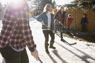 Smiling mothers playing ice hockey in sunny, snowy driveway - HEROF28964