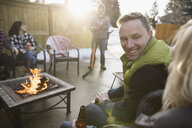 Smiling couples drinking beer at fire pit in snowy driveway - HEROF28967