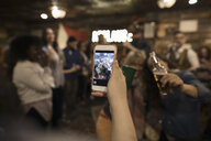 Woman with camera phone photographing friends at music concert - HEROF28982