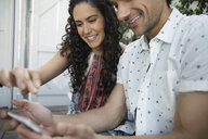 Smiling couple using smart phone - HEROF29012