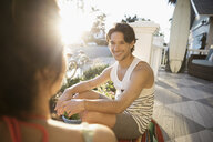 Smiling man talking to woman on summer beach house porch - HEROF29015