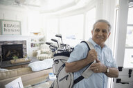 Smiling senior man carrying golf clubs in beach house - HEROF29018