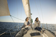 Women friends drinking champagne on sunny sailboat - HEROF29069