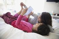 Smiling sisters using digital tablet on bed - HEROF29114