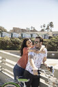 Smiling couple with bicycle hugging on sunny bridge - HEROF29141