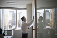 Businessman writing on whiteboard in highrise office - HEROF29222